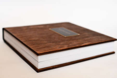 Big book with wooden cover of photo album, small depth of field. Фото со стока