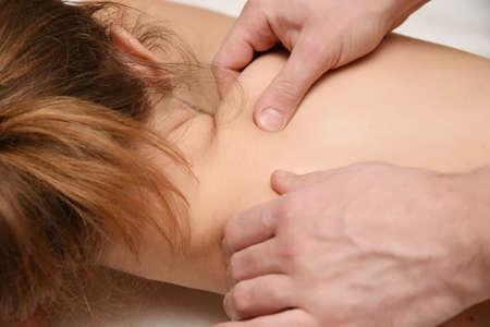 Male hands doing massage of girl close-up Фото со стока