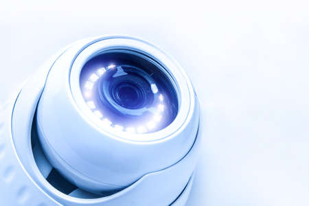 Security CCTV camera, tinted image in blue tones with light Фото со стока