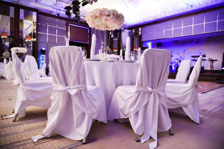 Banquet hall of the restaurant with furniture in white covers. Ceremonial hall of the restaurant Фото со стока