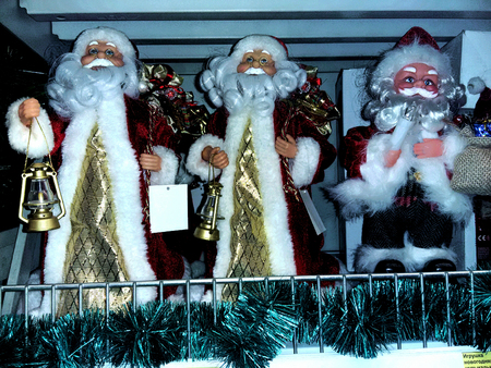 new years day: three Santa Claus on new years day stand in the window of a big store Stock Photo
