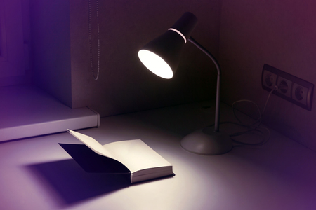 Lamp in socket and open book with a blank page for writing on white table in the evening or at night, toned in blue.