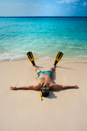Man, relaxing on the white sand beach in the clear sea water, lying on the water with yellow and black flippers fins and mask. After snorkeling Maldives beach Young Standard-Bild