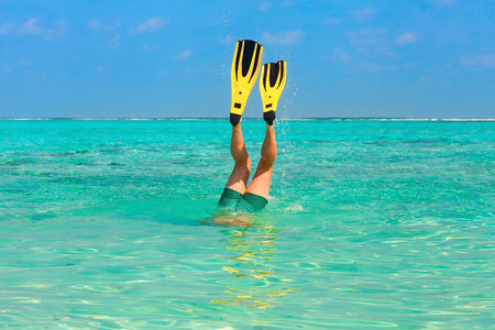plunges: Men dive snorkeling in clear water on the beach Islands with yellow flippers