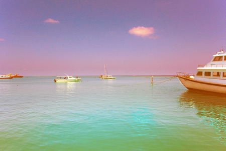 clear ocean water under blue sky whith boats and yacht