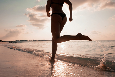 farther: Female Runner on the waves Beach at Sunset silhouette in air farther