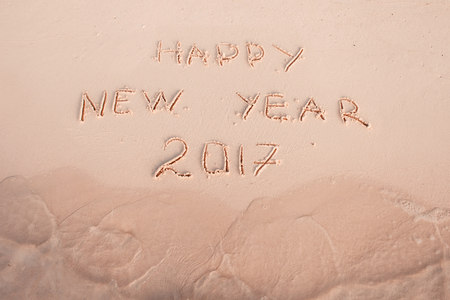 bahamas celebration: 2016 2017 inscription written in the wet yellow beach sand being washed with sea water wave. Concept of celebrating the New Year at some exotic place Stock Photo