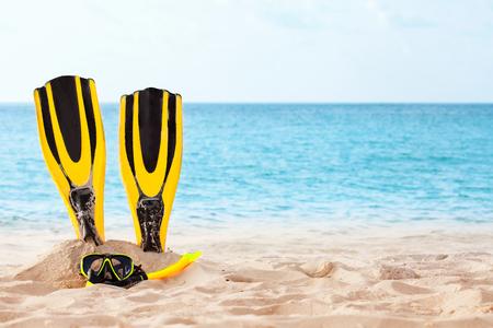 Geel masker met buis om te snorkelen en flippers op het strand