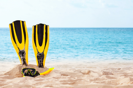 Yellow Mask with tube for snorkeling and flippers on the beach