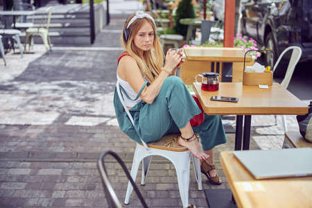 Side view of a wonderful pretty girl with headphones is drinking tea and listening to music and drinking tea at a cafe outdoors on a sunny day