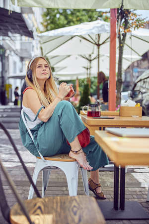 Pretty red-haired girl with freckles is listening to the music while sitting at the table in a cafe barefoot Stock Photo