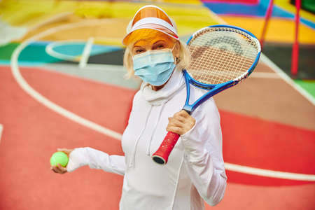 Old, healthy and cheerful lady on a colorfull square outdoors wearing mask and holding basketball ball