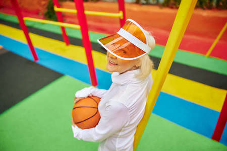 Old, healthy and cheerful lady with basketball ball on a colorfull square outdoors