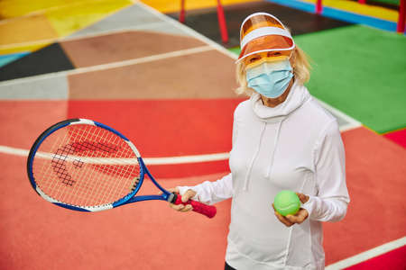 Old, healthy and cheerful lady on a colorfull square outdoors wearing mask and holding tennis racket with ball