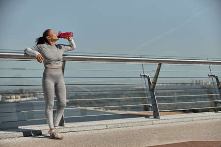 happy healthy and sporty woman is drinking water after workout trainings in sunny day