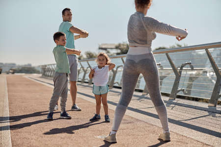 happy healthy and sporty family are doing workout trainings in sunny day