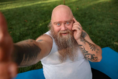 Fat caucasian bearded and bold man is doing morning exercses to loose his weight
