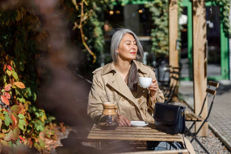 Mature pale hair stylish woman lifestyle portrait outdoors near cafe
