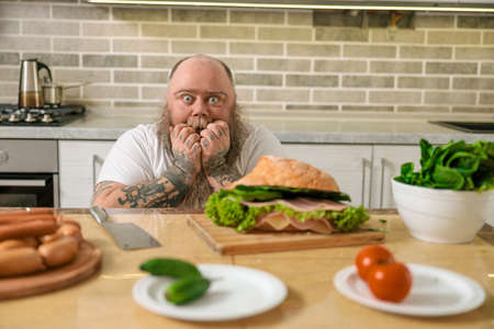 Emotional fat funny and tattooed man with food at the kitchen at home
