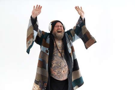 Fat stylish bearded tattoed caucasian man with big belly is posing and dancing wearing ethnic kimono Standard-Bild