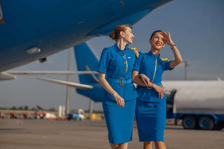 Two cheerful air stewardesses in bright blue uniform walking outdoors in front of passenger aircraft on a sunny day