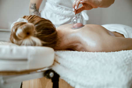 professional female specialist is doing cupping therapy on the back of beautiful caucasian lady Stock fotó