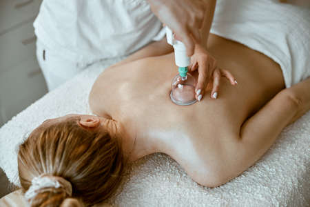 professional female specialist is doing cupping therapy on the back of beautiful caucasian lady