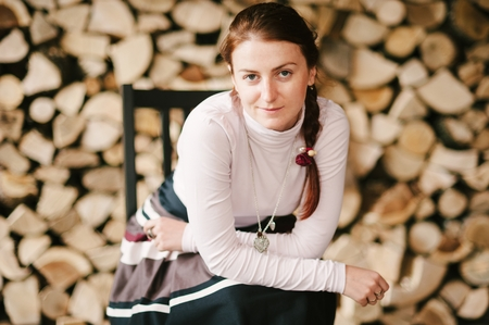 attitude girls: Close-up portrait of a woman posing by the pile of wood. Stock Photo