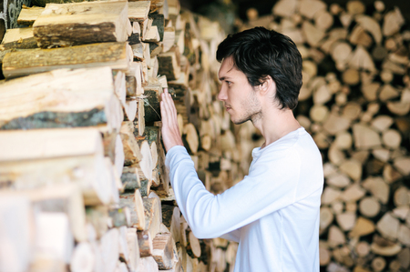 romantic man: Young man carefully touching the pile of wood. Stock Photo