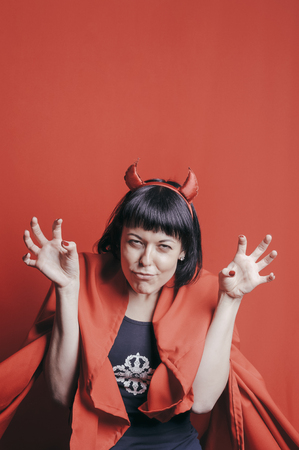 cope: Pretty young woman with devil horns and red cope growling. Woman with tricky expressing, looking straight. Red studio background.