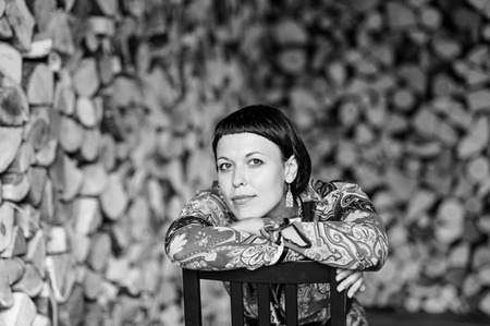 girl in nature: Smiled brunette woman  leaning on the wooden chair back. Short asymmetric hairstyle. Silver jewelry. Firewood background. Black and white style.