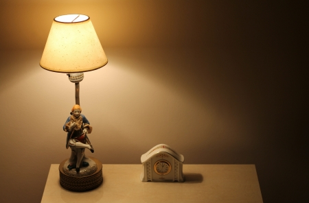 lamp and clock on the bedside table photo