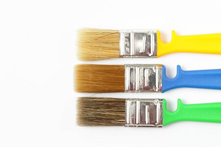 Paint brushes of different colors on a white background close-up, flat lay, place for text.