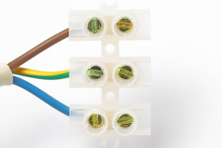Electrical terminal with connected wires close-up, white background.