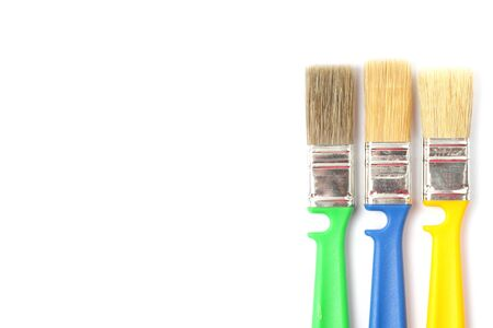 Colored paint brushes with plastic handles on a white background, place for text, isolate, flat layer, close-up.