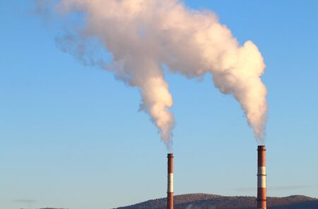Industrial chimneys with smoke on a background of blue sky, conservation and protection of nature and climate, concept.