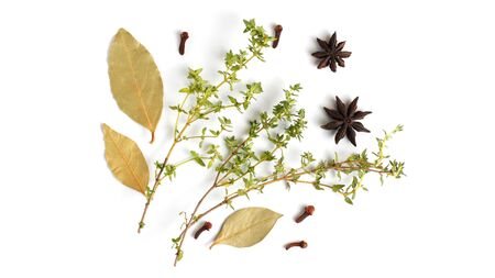 Fragrant herbs and spices on a white background. Bay leaf, cloves, allspice, thyme. Flat lay, top view, copy space. Stockfoto