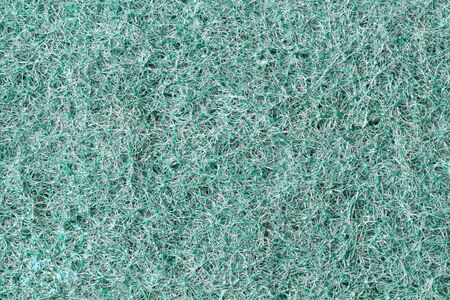 A surface with a hard pile, as a background, green color, close-up. Flat lay, top view, copy space.