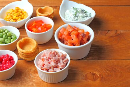 Ingredients for light meals, bacon, bell pepper, salmon, cheese with herbs, corn, tartlets. Wood table.