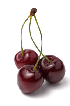 A bunch of sweet cherries from three berries with twigs on a white background, isolate, vertical frame, close-up.