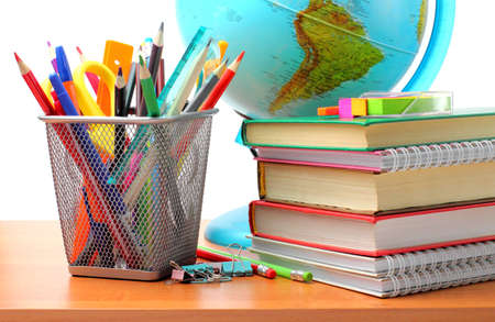 School supplies on the table, white background. Pencils, pens, rulers, globe, books and notebooks. Back to school concept.
