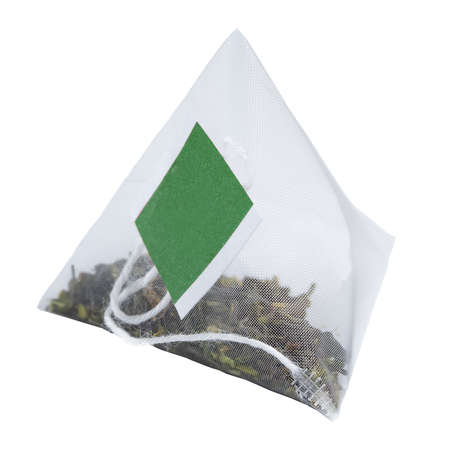Tea in a pyramid with a green label on a white background, close-up, place for logo or text. Banco de Imagens