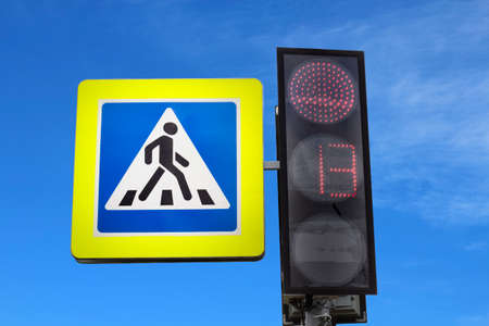 Pedestrian traffic light and crossing sign, red light at traffic light prohibiting signal. Backdrop of a blurry blue sky.