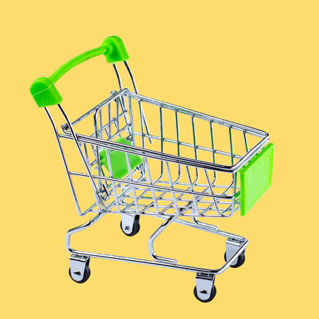 Shopping cart on a yellow background, isolate without shadow. Close-up, green design.