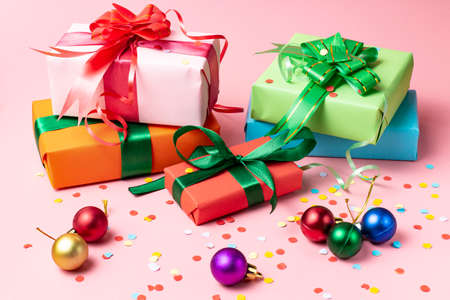 Christmas concept. Gifts in boxes in holiday packaging Christmas balls on a pink background.