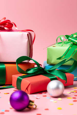 Christmas concept. Gifts in boxes in holiday packaging Christmas balls on a pink background. Place for text or congratulations.