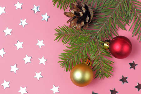 Christmas background, fir branch with cones, stars and Christmas balls on pink. Flat lay, top view. Stockfoto