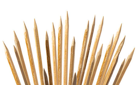 Wooden pointy stakes stick out in different directions on white.