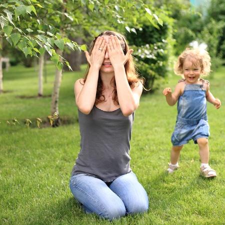 enfant qui joue: Femme et enfant jouant � cache-cache dans le parc de l'�t� Banque d'images