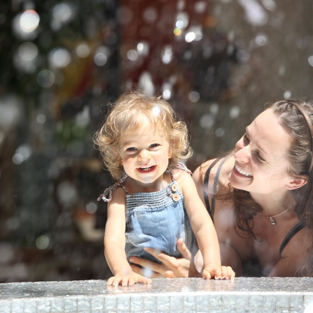 Happy child and woman in fountain splashes photo